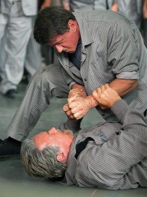 "Arnold Schwarzenegger and Sylvester Stallone brawl in a scene from ""Escape Plan."""