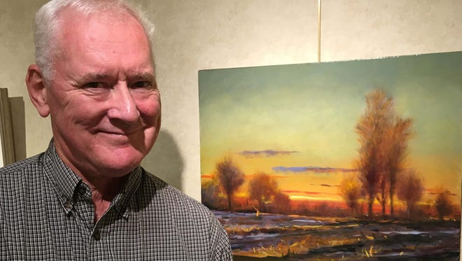 Artist Robert Buchanan with one of the oil paintings in his current exhibit at the Out Door Country Club.  The exhibit will be open through the end of October.