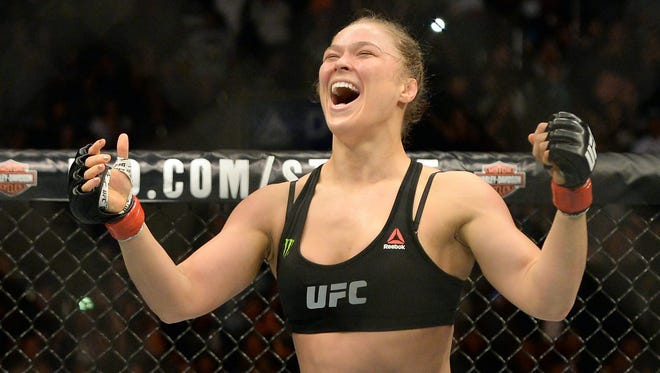 Ronda Rousey (red gloves) reacts after defeating Cat Zingano (not pictured) during their women's bantamweight title bout at UFC 184 at Staples Center. Rousey won in 14 seconds of the first round.