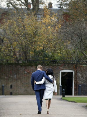 """In this Monday Nov. 27, 2017 file photo Britain's Prince Harry and Meghan Markle walk away after posing for the media in the grounds of Kensington Palace in London. In a stunning declaration, Britain's Prince Harry and his wife, Meghan, said they are planning """"to step back"""" as senior members of the royal family and """"work to become financially independent."""" A statement issued by the couple Wednesday, Jan. 8, 2020 also said they intend to """"balance"""" their time between the U.K. and North America."""