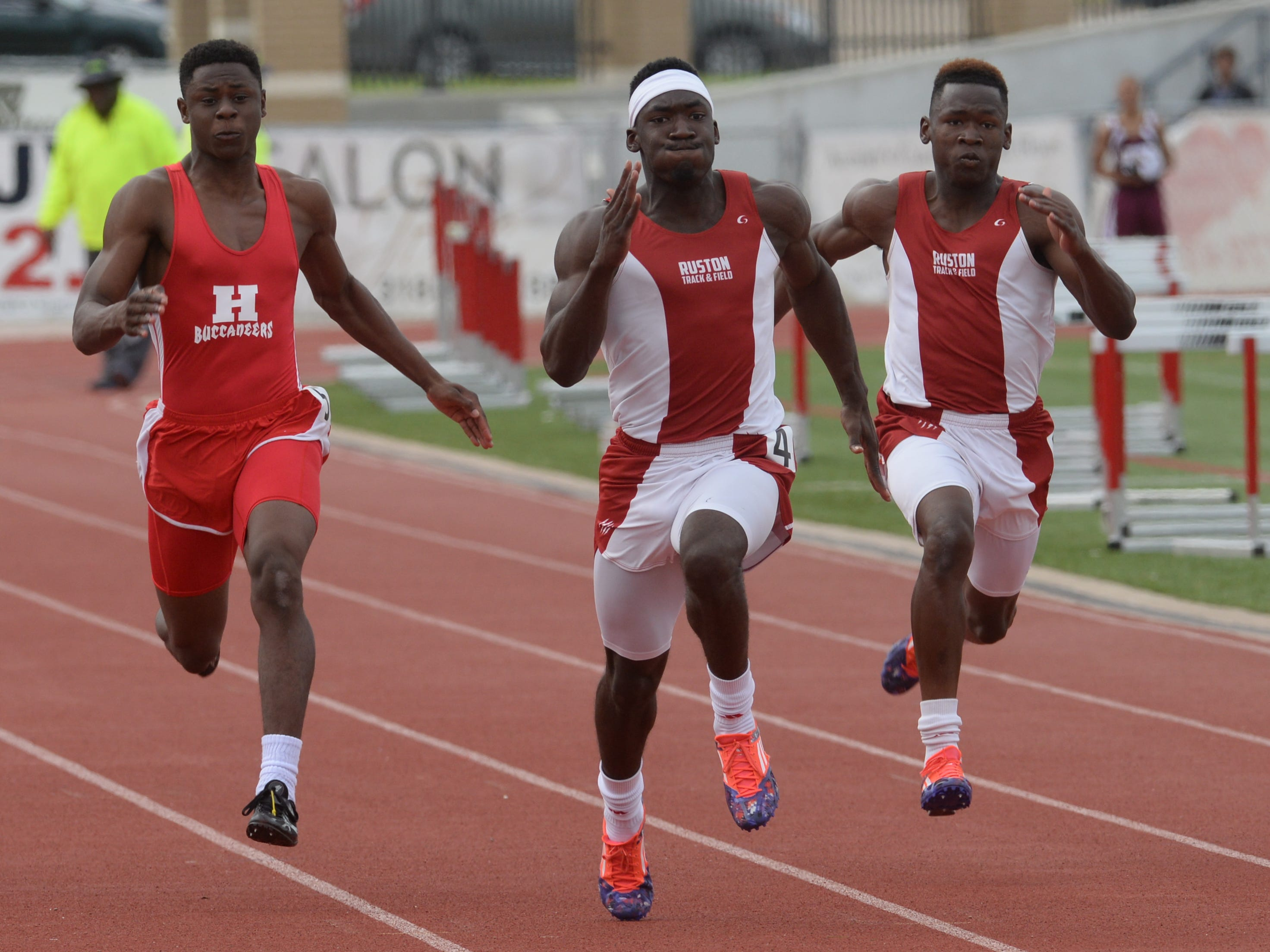 Keitaivous Walter (center) edges out Josh Lister of Haughton and his brother Kemondrick Walter in the 100m dash.