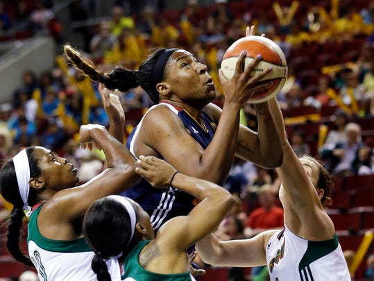 Connecticut Sun's Kelsey Bone, center, comes down with a rebound into a crowd of Seattle Storm players during the first half of a WNBA basketball game Tuesday, July 15, 2014, in Seattle. (AP Photo/Elaine Thompson)