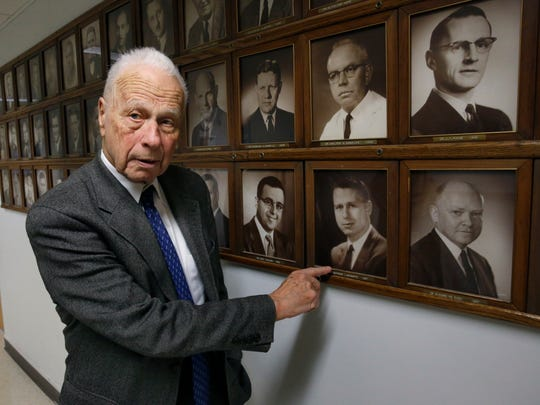 Dr. Seymour Schwartz, a URMC retired surgeon who turns 90 on Jan. 22, points at a portrait of himself from 1957 at Strong Memorial Hospital.