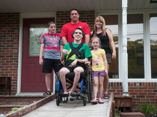 Dave and Sue Goldstein with their children, from left, 14-year-old Ryan, 18-year-old son Joshua, and 5-year-old Jessica outside of their Voorhees home.  Joshua and Ryan both have Joubert syndrome, a rare brain malformation characterized by the absence or underdevelopment of the cerebellar vermis, an area of the brain that controls balance and coordination, as well as a malformed brain stem.   Joshua's condition is more severe than Ryan's.   Joshua is confined to a wheelchair and his parents are raising money to buy a new handicapped accessible van because their current van requires costly upkeep which poses a financial strain on their budget.   05.27.14
