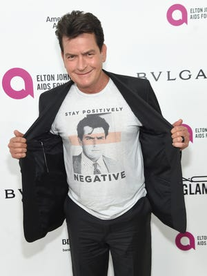 Charlie Sheen shows off his T-shirt on the ivory carpet.