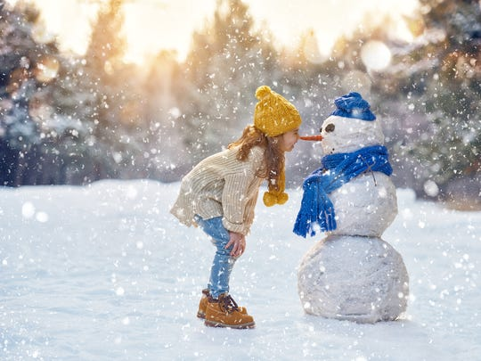 A little girl playing in the snow with a snowman.