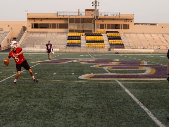 Shasta quarterback Ian Garcia, left, warms up Friday