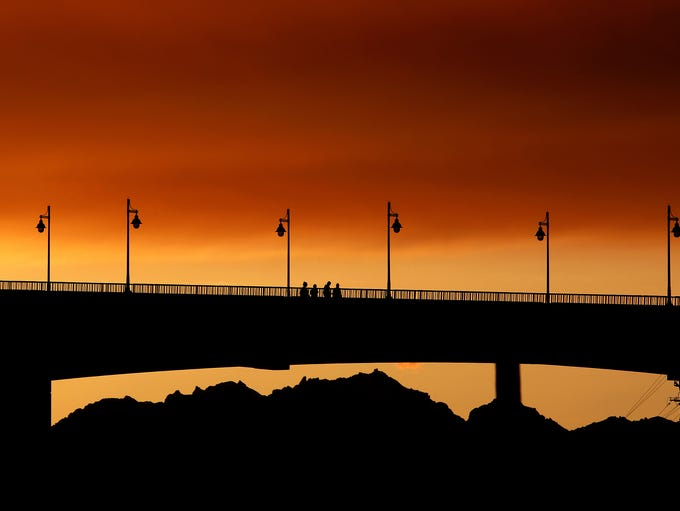 Pedestrians cross the Manette Bridge at sunset on Saturday,