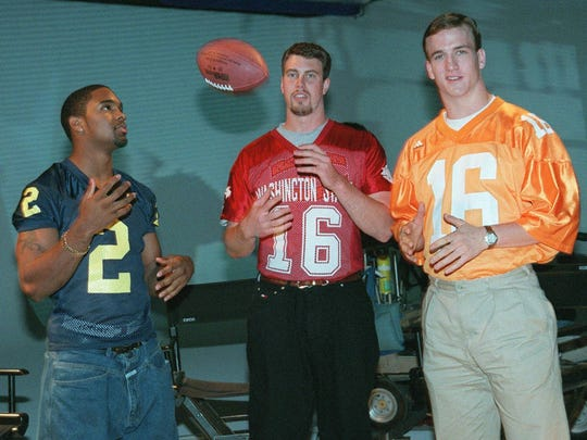 Heisman trophy winner Charles Woodson, left, of Michigan, banters with quarterbacks Ryan Leaf, center, of Washington State and Peyton Manning of Tennessee after shooting a commercial to promote ESPN's coverage of the NFL draft Monday, April 6, 1998, in New York. Draft selections will be made on April 18 and 19 in New York. (AP Photo/Steve Friedman, ESPN)