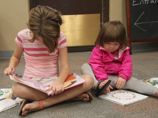 McKenzie Hodges, 8, and Kensley Snowden check out the books they received at the summer reading program registration on Thursday.