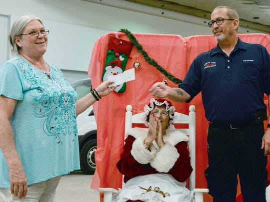 PATCHES PPEC RN Administrator Gail Steward, left, accepts a generous contribution from the Port St. Lucie Police Athletic League President John Briney as Mrs. Claus Jane Rowley cheers them on at Fort Pierce's Orange Blossom Mall.