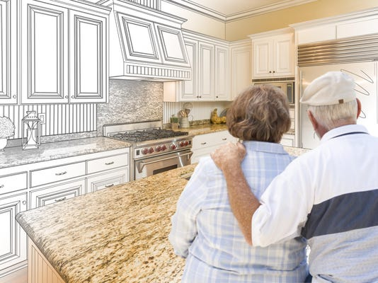 Senior Couple Looking Over Custom Kitchen Design Drawing and Photo
