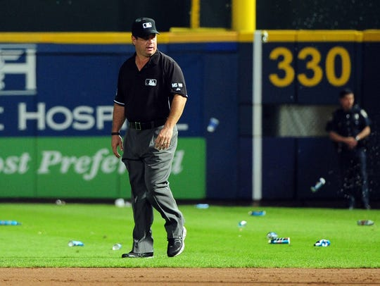 Umpire Rob Drake reacts after bottles are thrown on
