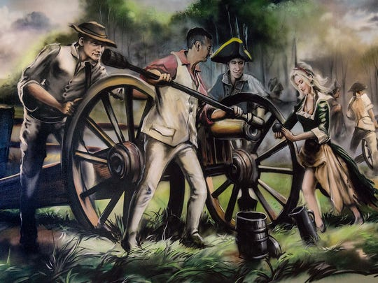This scene, inspired by the Revolutionary War story of Molly Pitcher includes figures of Ed Swadish, holding the ram, sons Nick and Spencer, and Ed's wife Sandy, at right. It's painted on the wall of Molly Pitcher's Dining inside Huron Valley Guns.