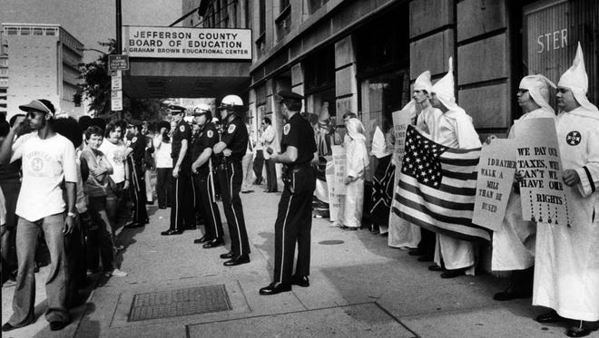 Bud Kamenish/The Courier-Journal An anti-busing demonstration by Ku Klux Klan members in front of the county Board of Education building, Aug. 22, 1975, sparked some heckling, but no other incidents. Police arrived at the end of the 65-minute demonstration and stood between Klan members and a crowd composed mainly of curious bystanders. The 12 robed Klan demonstrators included Kentucky Grand Dragon Phillip Chopper, his wife and five children. Klan members were silent. An anit-busing demonstration by KuKlux Klan members in front of the county Board of Education building this morning sparked some heckling, but no other incidents. Police arrived at the end of the 65-minute demonstration and stood between Klan members anda crowd composed mainly of curious bystanders. The 12 robed Klan demonstrators included Kentucky Grand Dragon Phillip Chopper, his wife and five children. There were some non-robed sympathizers. The Klan members were silent during heckling from both blacks and whites.  8/22/75