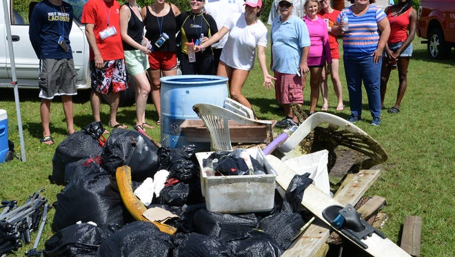 Volunteers show the trash they collected from Sykes Creek during a river cleanup event hosted by Keep Brevard Beautiful and Florida Today.