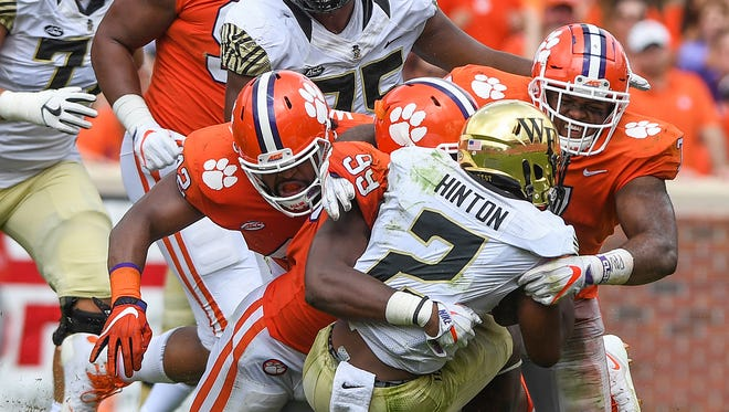 From left, Clemson defensive lineman Christian Wilkins (42), defensive lineman Clelin Ferrell (99), and defensive lineman Austin Bryant (7) bring down Wake Forest quarterback Kendall Hinton (2) during the 3rd quarter on Saturday, October 7, 2017 at Clemson's Memorial Stadium.