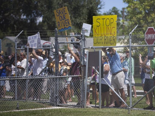 Chain linked fences seperated protesters and the media from Gov. Rick Scott and Sen. Joe Negron as they toured part of the St. Lucie River near Stuart on Aug. 20, 2013, to access the environmental impact of water being released from Lake Okeechobee. (AP Photo File/J Pat Carter)