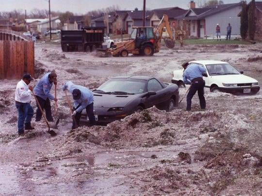 City workers dig out cars on Tres Rios Drive from hail that fell in May 1995.