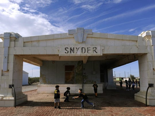 Children play pass a football beneath the overhang of the Snyder Santa Fe Depot while other family members pose for pictures beside the structure in 2016. The building was a cultural touchstone for the community until its demolition in 2017.