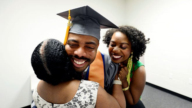 Ferrell Lewis, 36, hugs his mother Darline Lewis, 60, as his sister Feylyn Lewis joins in before the start of the commencement ceremony at Volunteer State Community College, Saturday, May 6, 2017, in Gallatin, Tenn. His sister flew to Tennessee from England to surprise Ferrell Lewis, who dropped out of Tennessee Tech 18 years ago to help support his mother and sister.