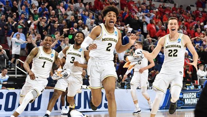 Michigan Wolverines guard Jordan Poole (2) celebrates with teammates after making the game-winning three-point shot to defeat the Houston Cougars.