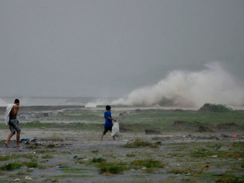 Residents sift through the shoreline amid a storm surge brought about by powerful Typhoon Haiyan.