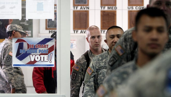U.S. Army soldiers, members of the NATO-led peacekeeping force in Kosovo, walk inside a dining facility where posters urge them to vote in the military Camp Bondsteel in Sojevo, Kosovo on Friday, Nov. 2, 2012. U.S peacekeepers cast early ballots in elections.