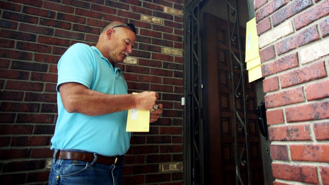 City code inspector Dale Wood issues citations for over-occupancy under the you-plus-two law at a home on Parklake Drive and Yucca Street on July 14.