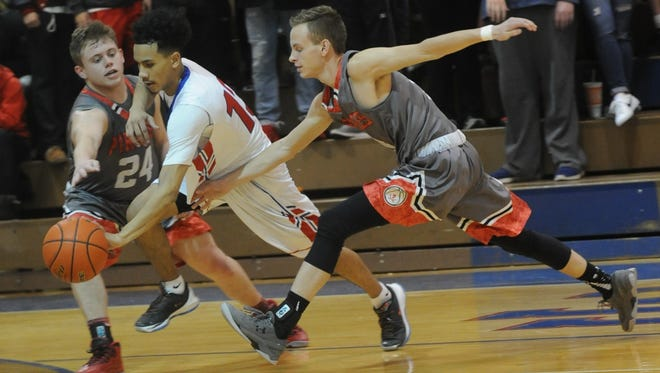 Abilene Cooper's Isaac Moreno, center, tries to drive between Lubbock Cooper's Braden Buckley, left, and another Pirate. The Cougars beat Lubbock Cooper 62-50 in a District 4-5A boys basketball game Friday, Jan. 27, 2017 at Cougar Gym.