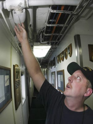 Chief engineer Lt. Greg Tarpey inspects a leaky pipe aboard the Coast Guard Cutter Decisive in 2005. Many of the Coast Guard's ships have old, broken equipment with rust and leaking pipes.