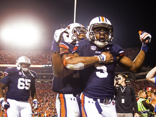 Auburn quarterback Nick Marshall (14) grabs wide receiver Ricardo Louis (5) after Louis scored the game-winning touchdown against Georgia at Jordan-Hare Stadium on Saturday, Nov. 16, 2013 in Auburn. Ala.