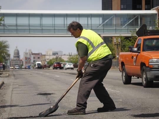 Richard Reid of the City of Lansing fills potholes