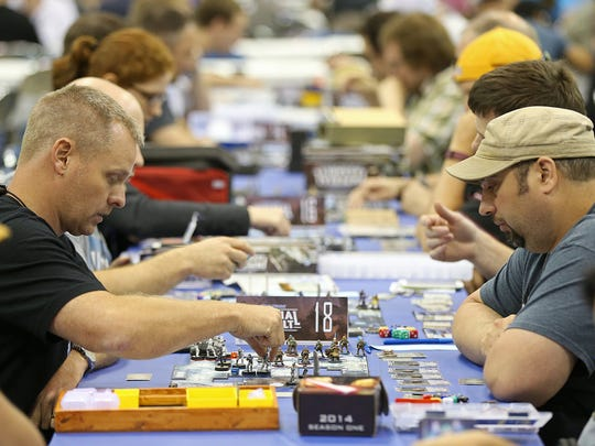 Convention-goers play tabletop games during Gen Con at the Indiana Convention Center, Indianapolis, Saturday, Aug. 6, 2016.