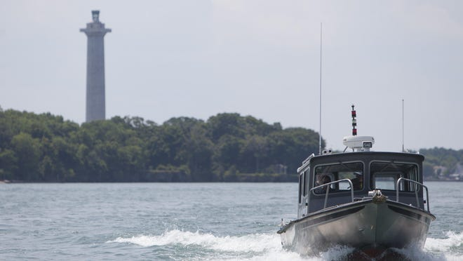 A boat speeds away from South Bass Island, home to Put-in-Bay. Perry's Victory and International Peace Memorial rises from the Lake Erie tourist stop.