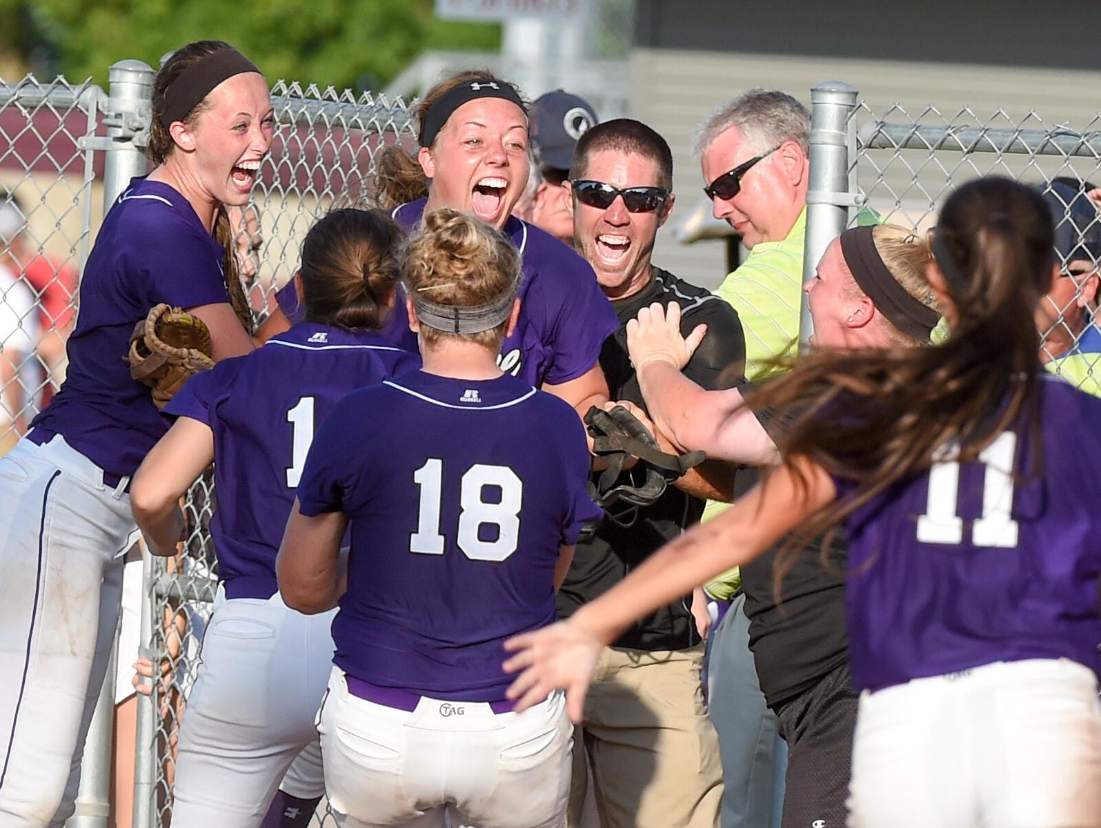 Waukee players and coaches celebrate after the Warriors won the Class 5-A state softball title.