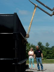 Owner of Braco, Brittany Hazelwood, left, and David Wicker, stand back for the rotation of a newly arrived dumpster Friday morning.