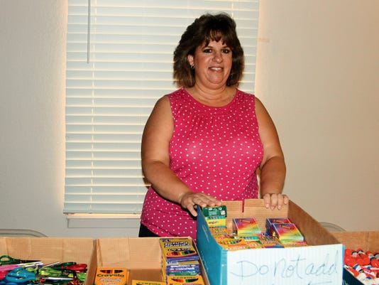 Love INC of Otero County Executive Director Susan Payne goes through donations for the Aug. 8 school supplies give-away.