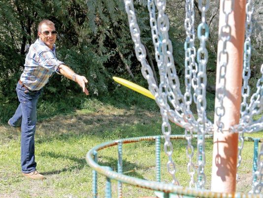 Jacob Chavez, developer of Majestic Enchantment, tosses a disc into a handmade disc golf basket on Sept. 11 at the property in Turley.
