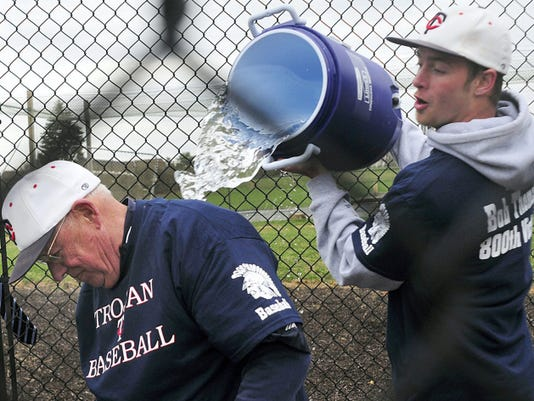 Chambersburg coach Bob Thomas gets a ceremonial bath following his 800th career victory on April 15, 2013. Trojan player Tyghe Bowers performed the honors. Thomas resigned Tuesday after 51 years as the head coach.