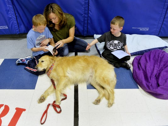 Pam Cooley of Windsor Township, center, helps her 8-year-old son Caden read as 6-year-old Rylan pets Callie, a 7-year-old therapy golden retriever belonging to Sue and Emery Grove of Red Lion on Wednesday at Locust Grove Elementary. The Paws for a Night of Reading and Writing evening program highlighted a new school-wide initiative to emphasize literacy.
