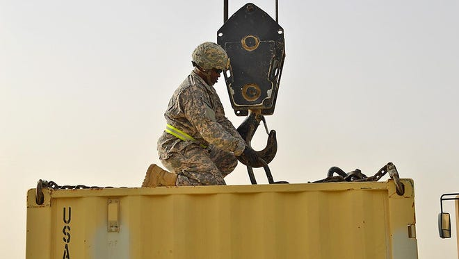 Staff Sgt. Jeremy D Robinson of Monroe places the load on the hook so that the operator may prepare to lift the load. He was assigned to Forward Support Company of the 528th Engineering Battalion.