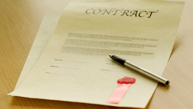 Contract and pen on table.