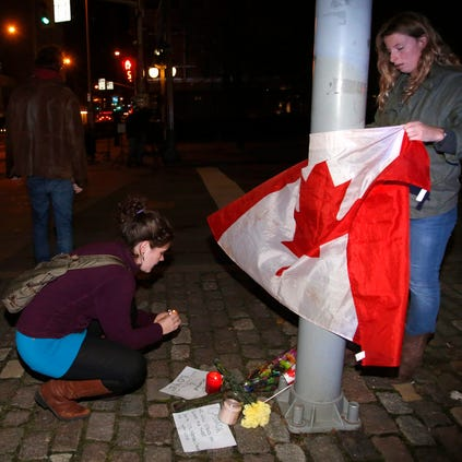 Mourners light a candle and tie a Canadian flag around