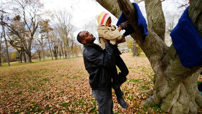 Charles Fallin lifts Arielle Fallin, 8, of New Freedom, so she can place a blanket on the branch of a tree at Farquhar Park in York. The group, Coats of Friendship, distributed over 700 coats at LifePath Christian Ministries, Penn Park, Farquhar Park and Albermarle Park on Saturday.
