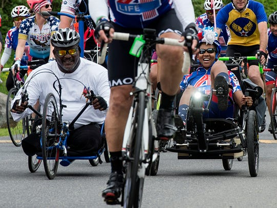 Shanda Taylor Boyd, right, and Gregory Gadson, both U.S. Army veterans, smile as they approach the finish line, Sunday, April 29, 2017. Hundreds participating in World T.E.A.M Sports' Face of America bicycle and hand cycle ride to Gettysburg raised over $500,000.