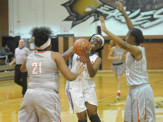 Cooper's Daniece Edwards, center, drives for a shot