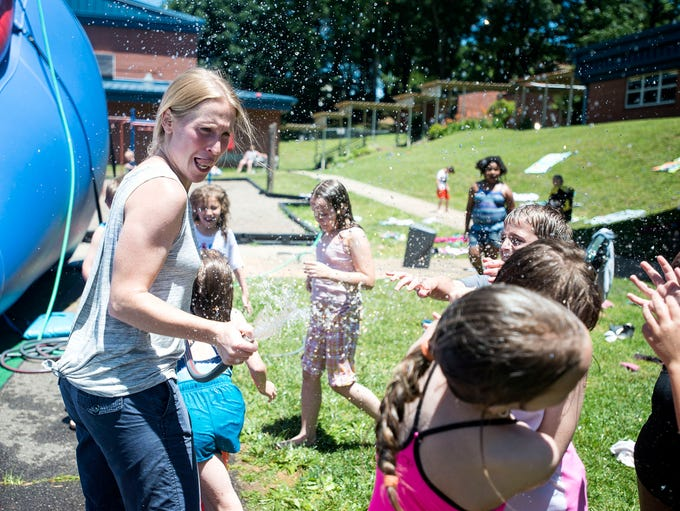Grayson Chell makes a face as she sprays water from