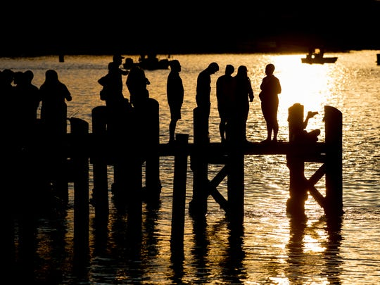 A crowd gathers on a pier just before the start of the Chincoteague Pony Swim on Wednesday, July 26, 2017.