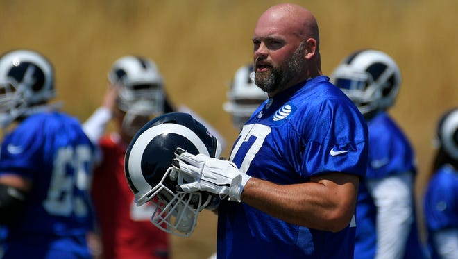 In this May 30, 2017, file photo, Los Angeles Rams tackle Andrew Whitworth stands on the field during NFL football practice, in Thousand Oaks, Calif. Although the left tackle is four years older than his new head coach, he couldn't resist the challenge and adventure of helping to rebuild the NFL's worst offense on the West Coast.